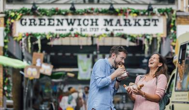 A couple enjoy food at Greenwich Market.