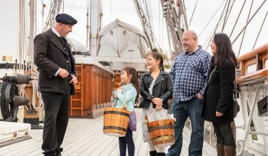 A family speak to the captain of the Cutty Sark in Greenwich.