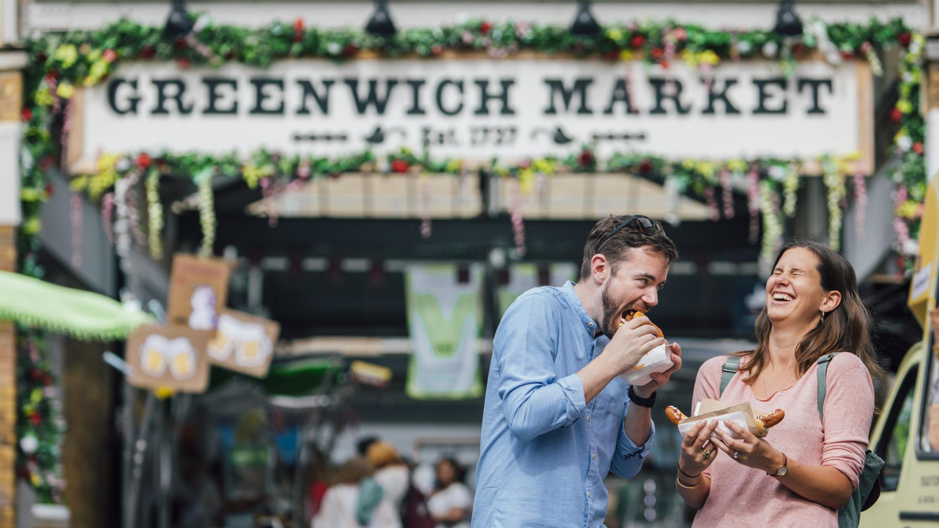 A couple eat food from the Food Court at Greenwich Market.