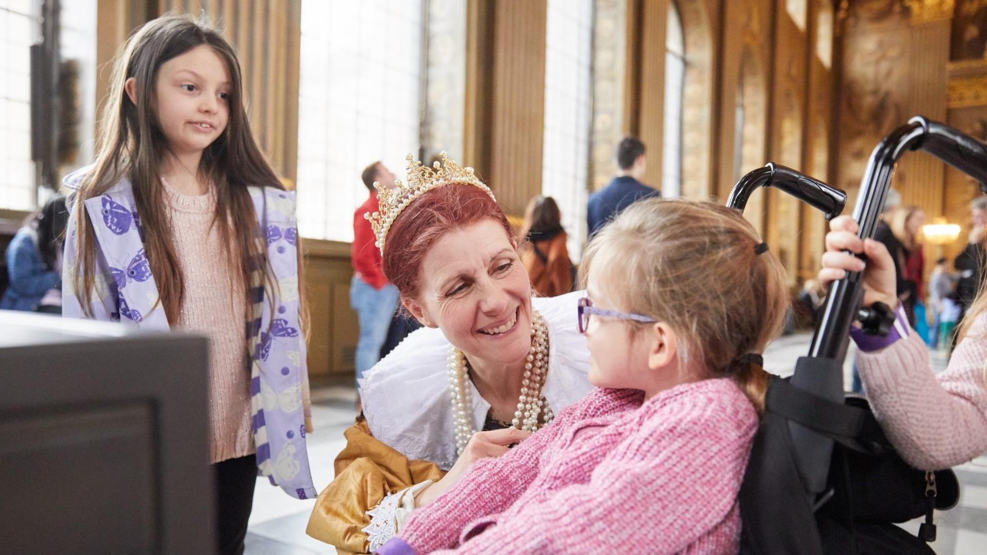 A young girl in a wheelchair is greeted by staff at the Painted Hall at the Old Royal Naval College in Greenwich.