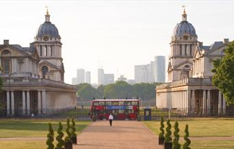 A London Bus centre aligned between Old Royal Naval College domes in Greenwich looking toward the river Thames in Greenwich