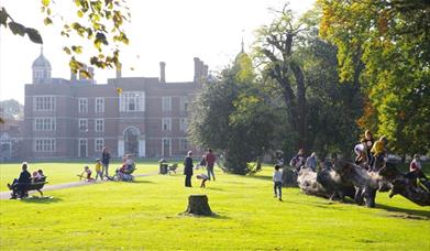 Kids playing beside Charlton House in Charlton Park and Parents relaxing on benches on a beautiful Sunny Day