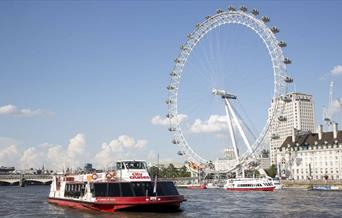 Red and white City Cruises boat on the River Thames passing the London Eye