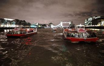 Two City Cruises boats on river Thames at night with lit up Tower Bridge in the background.