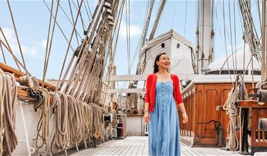 A lady stands on the upper deck of Cutty Sark in Greenwich, London.
