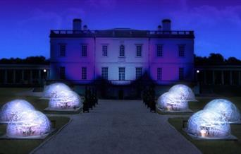 Night view of the Queen's House with eight Dining Domes set on the grounds in front of the art gallery.