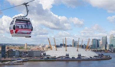 Emirates Air Line carrier on top of river Thames, overlooking The O2 which is a white dome with 12 yellow pillars around on top.