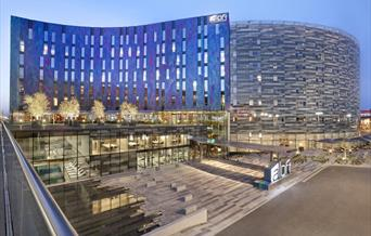 Main view of the hotel's deep blue and purple exterior in the evening in London's Docklands.