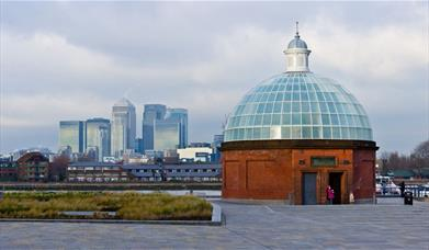 Image shows Greenwich Foot Tunnel made of red bricks with a dome made of matte finished glass.  In the background you can Canary Wharf skyline.