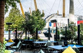 Outside seating at Greenwich Kitchen Bar & Grill in a modern and intimate setting looking out onto a vibrant Balearic themed terrace and The O2 arena.