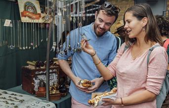 A couple admire the jewellery on a stand at Greenwich Market with some fresh street food in-hand.