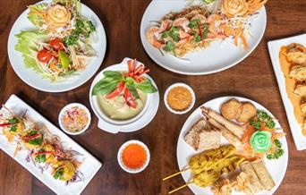 Table set with Kathi Thai Kitchen specialities including appetisers platter, papaya salad, green curry and more.
