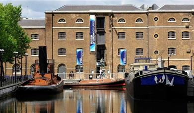 Museum of London Docklands building by the river with small boats taxied in front of it.