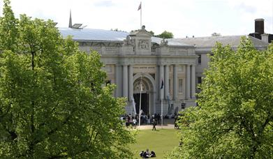 The grand exterior of the National Maritime Museum in Greenwich, surrounded by beautiful trees and a family having a picnic outside.