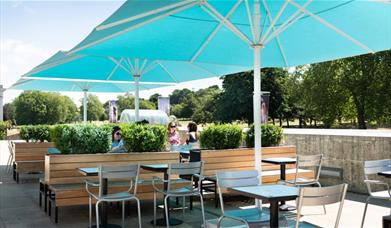 Outside seating at the Parkside Cafe, showing multiple seating areas, benches and the option for big umbrellas.