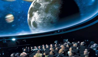 People sit in awe under the stars projected on the ceiling of the Peter Harrison Planetarium.