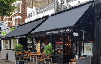 Pizza Express Blackheath, showing a blacked out restaurant with outdoor and indoor seating.