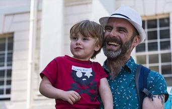 Father and son at a session of Play Outdoor Tuesdays on the grounds of Royal Museums Greenwich outside National Maritime Museum.