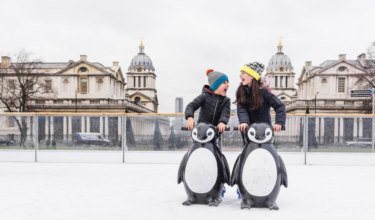 Two children laughing as they hold onto model penguins to steady themselves on the ice at the Queen's House Ice Rink in Greenwich.