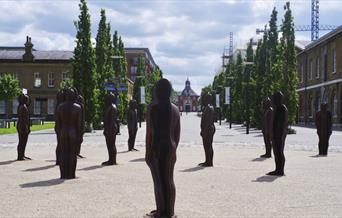 "A view along Number One Street in Royal Arsenal, Woolwich, featuring the famous ""Assembly"" statues by Peter Burke."