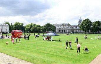 Red bus and people stood on green grass on the Royal Museums Greenwich Grounds