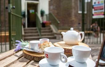A teapot and teacups laid out on a table outside Severndroog Castle in the sunshine.