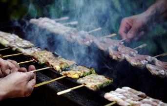 Small wooden sticks of meat, fish and cheese being grilled over open flame at Sticks'n'Sushi.