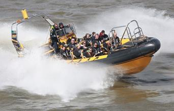 Black and yellow Thames RIB speedboat in action on river Thames.