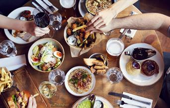 A group sit around a table full of delicious food and drink at The Admiral Hardy.