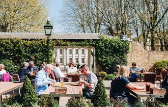 People sit for lunch and a drink in the beautiful walled garden outside The Old Brewery in the sunshine.
