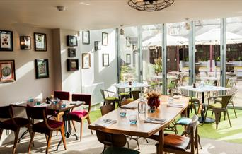The dining room at The Pilot is bright and airy and overlooks the garden through floor to ceiling glass doors.