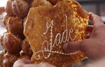 In the image, the Jade Boulangerie pastry chef is adding a display with 'Jade' written to the stack of profiteroles.