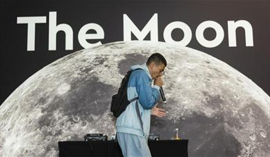 Youth artist with a mic in his hand facing right side in front of 'The Moon' banner.