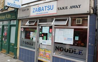 Image showing the entrance of Zaibatsu Japanese Fusion Restaurant with menu displayed on the glass window.