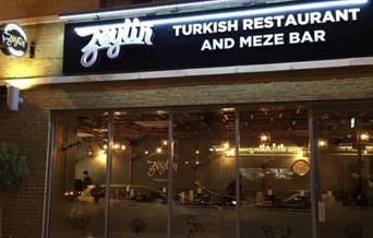 Exterior image of Zeytin Restaurant with glass entrance and warm lighting.