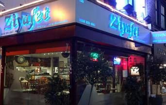 Night view of entrance of Ziyafet Restaurant exterior with big glass window around and name glowing with blue light in the background.